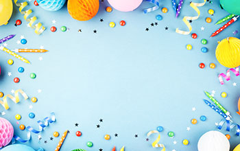Birthday party blue background. Frame made of colorful serpentine, balloons, candles, candies and confetti.